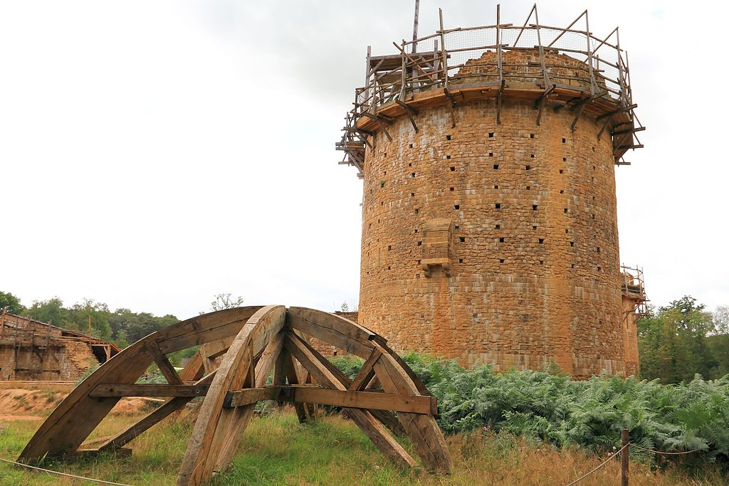 Picture of a brown stone medieval tower under construction.
